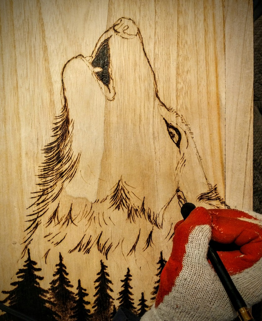 The artist burning an image of a howling wolf onto wood.