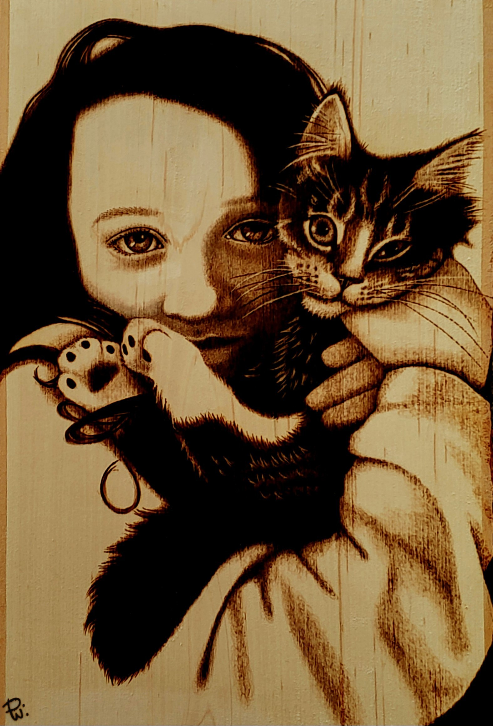 Pyrographic image of young girl cuddling her kitten