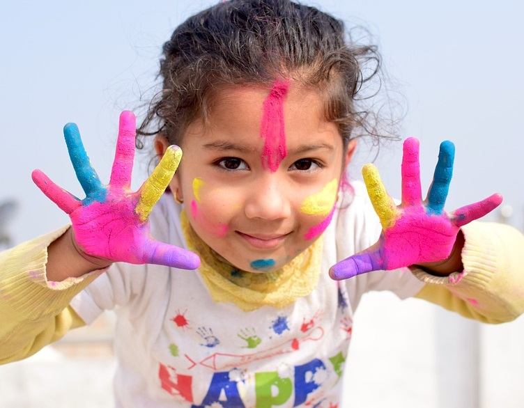 Young, smiling girl with painted hands and face.